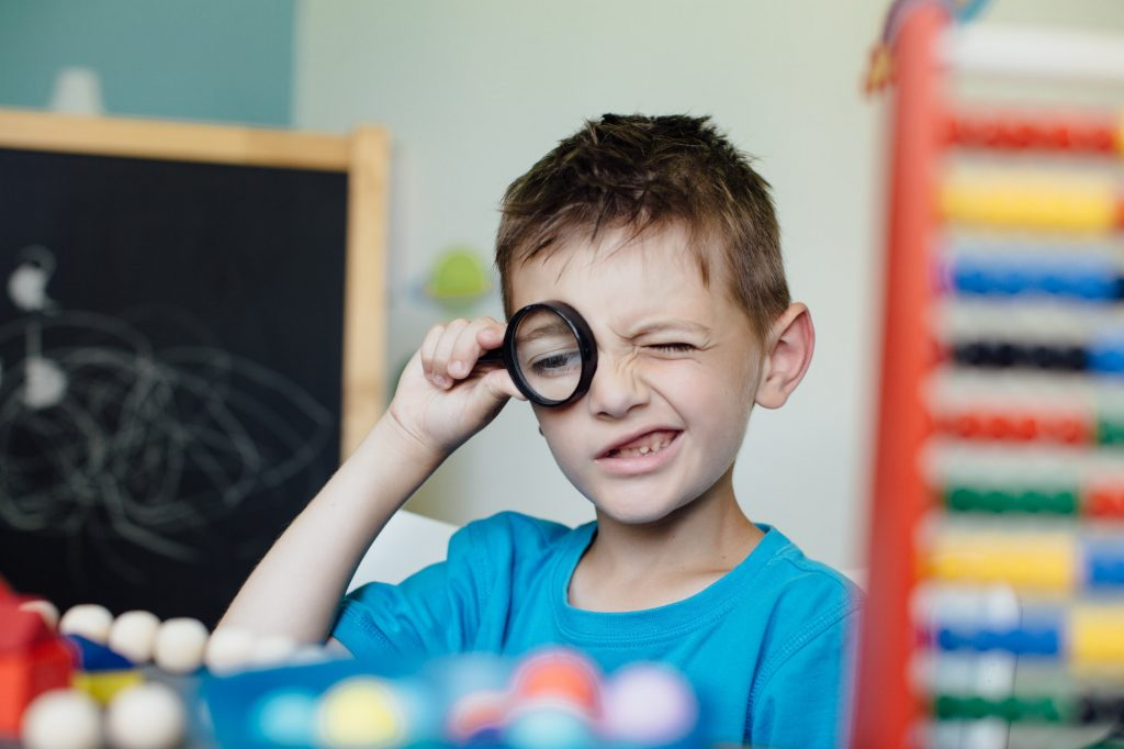 Schoolboy looking through a magnifying glass